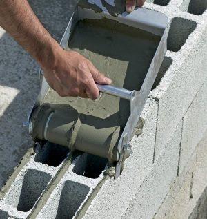 application de la colle à parpaing au rouleau applicateur